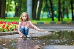 小愉快的女孩获得乐趣在一个大水坑  图库摄影