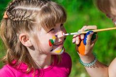 小愉快的姐妹使用与颜色在公园,儿童游戏,儿童油漆 免版税图库摄影