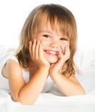 小愉快的微笑的快乐的女孩在被隔绝的床上 免版税库存图片