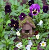 小手在庭院里制作了有夏天花的逗人喜爱的房子 免版税图库摄影