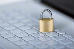 小挂锁坐白色键盘,网上安全概念 免版税库存图片