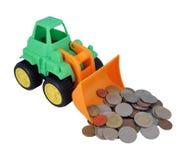 小推土机玩具 推土机玩具和硬币 免版税库存图片