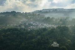小掩藏在山的picturescue北意大利村庄当早晨雾上升  免版税库存照片