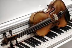 小提琴在背景的钢琴钥匙 库存照片