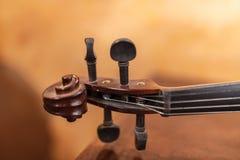 小提琴有串和调整的钉的仪器把柄在温暖的光下 免版税图库摄影