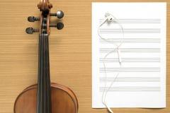 小提琴和与耳机的乐谱用纸笔记顶视图  库存图片