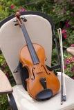 小提琴和弓在椅子 免版税库存图片