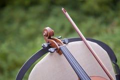 小提琴和弓细节在椅子 免版税库存图片