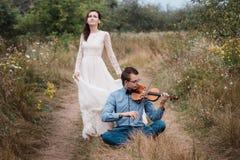 小提琴手和妇女白色礼服的,年轻人在小提琴演奏背景自然 图库摄影