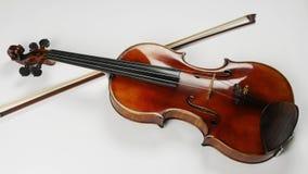 小提琴的顶视图和在它附近的一把弓 在小提琴下的弓 股票录像