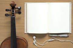 小提琴笔记本和耳机顶视图  免版税图库摄影