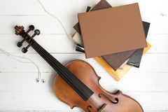 小提琴顶视图有堆的书和耳机 图库摄影