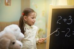 小教师 美丽的女孩在家教玩具  库存图片
