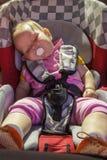 小新出生的女婴在汽车座位休息 免版税库存照片