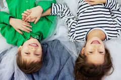 小朋友、男孩和女孩说谎并且笑 爱的概念 库存照片