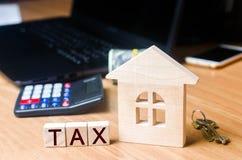 小木房子和税在桌面上 在房地产,付款的税 惩罚,欠款 纳税人记数器物产的 免版税库存图片