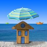 小木房子在与伞海滩-概念imag的海边 免版税库存图片