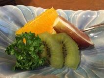 小果实盛肉盘特写镜头用猕猴桃、桔子和西番莲果 免版税库存图片
