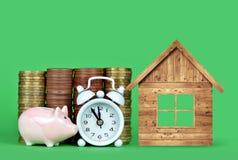 小桃红色存钱罐、堆硬币,白色闹钟和木房子绿色背景的 免版税库存照片