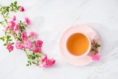 小桃红色玫瑰茶和分支在土气桌上的 平的位置 库存图片