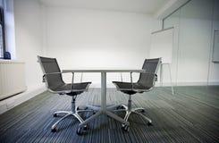 小桌和两把椅子侧视图在办公室 免版税库存照片