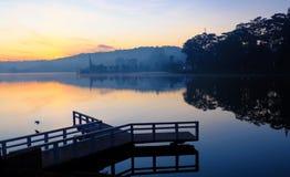 小桥梁在湖反射在日出 免版税库存图片