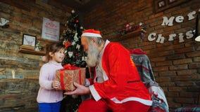 小欧洲女孩在圣诞老人` s圣诞节愿望耳语 r 图库摄影