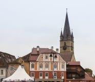 小正方形的片段与圣玛丽路德教会的大教堂clocktower的在一个雨天在锡比乌市在罗马尼亚 库存照片