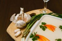 小毒蛇,装饰用红萝卜,在木背景的荷兰芹 与月光,伏特加酒,大蒜,大葱的俄国全国食物 免版税库存照片
