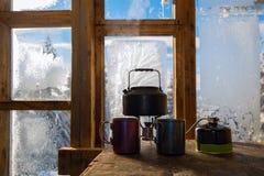 小水壶在煤气喷燃器站立在钢杯子旁边 库存图片
