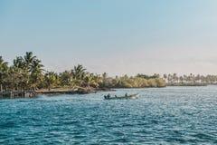 小汽艇的两个人在有热带棕榈树的海洋 图库摄影
