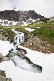 小河切开在高山cirque的雪桥梁下 图库摄影