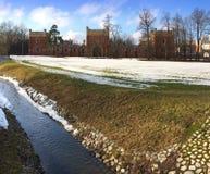 小河在春天在解冻的雪框架流动  亚历山大公园,圣彼德堡的郊区 免版税库存图片
