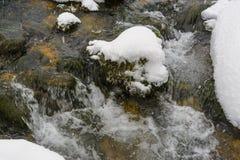 小河流经随风飘飞的雪 库存照片