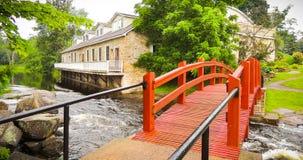 小河跑通过磨房和在一座红色脚桥梁下 免版税库存照片