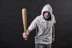 小流氓在hoody,时尚的穿戴敞篷 人举行棒球棒,侵略 匪徒人威胁与棒武器 侵略,愤怒 免版税图库摄影