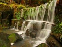 小测流堰小瀑布在山小河,水的跑在砂岩块,并且泡影创造乳状水。 库存图片