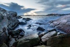 小海湾在Helleviga度假区、岩石和石头在海洋,蓝色小时在南挪威 库存图片