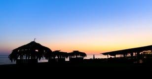 小海滨的小屋和餐馆剪影有芦苇屋顶的在日落 免版税图库摄影