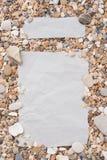 小海石头和壳在中心,在,与一个自由空间在文本、标题、广告、菜单或者图片下在织地不很细 免版税库存照片