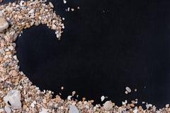 小海石头和壳在左角从,在黑背景,与一个自由空间在文本下,标题,广告 库存图片