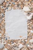 小海石头和壳在织地不很细纸在中心,与一个自由空间在文本、标题、广告、菜单或者图片下 库存照片