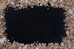 小海石头和壳,在黑背景,与一个自由空间在文本、标题、广告、菜单或者图片下 免版税图库摄影
