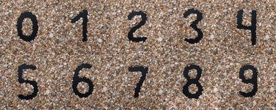 以小海滩石头为背景的黑数字,设计师和装饰员的 免版税库存图片