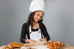 小深色皮肤的女孩滚动面团 孩子学会烹调 衣物和厨师帽子 库存图片