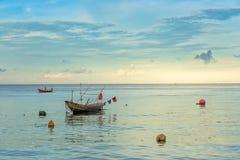 小渔船在日落期间的海 免版税库存照片