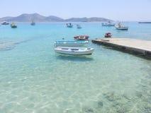 小渔船在水晶水海 免版税库存照片