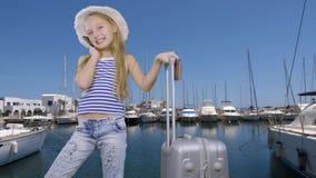 小游人谈话在电话,当走带着在码头的手提箱与游艇时 影视素材