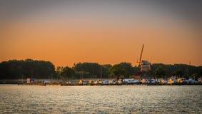 小游艇船坞和风车在日落 图库摄影