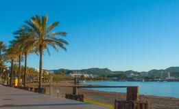 小游艇船坞&海湾在St安东尼de Portmany,伊维萨岛,巴利阿里群岛,西班牙 沿木板走道的镇静在温暖,晚天太阳的水&海滩 免版税库存图片